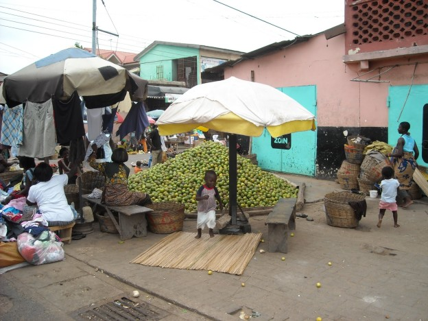 Informal vendors sell fruits at periphery of Kaneshie Market, Accra, Ghana.