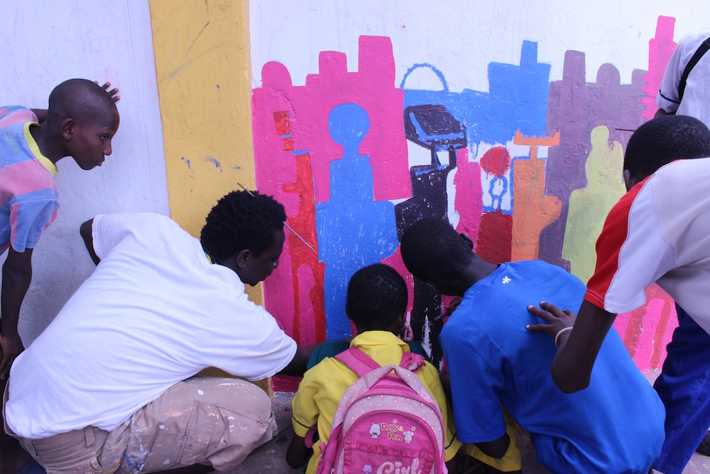 Musah Swallah, a local artist and leader in NMA, paints with Nima youth along the wall.