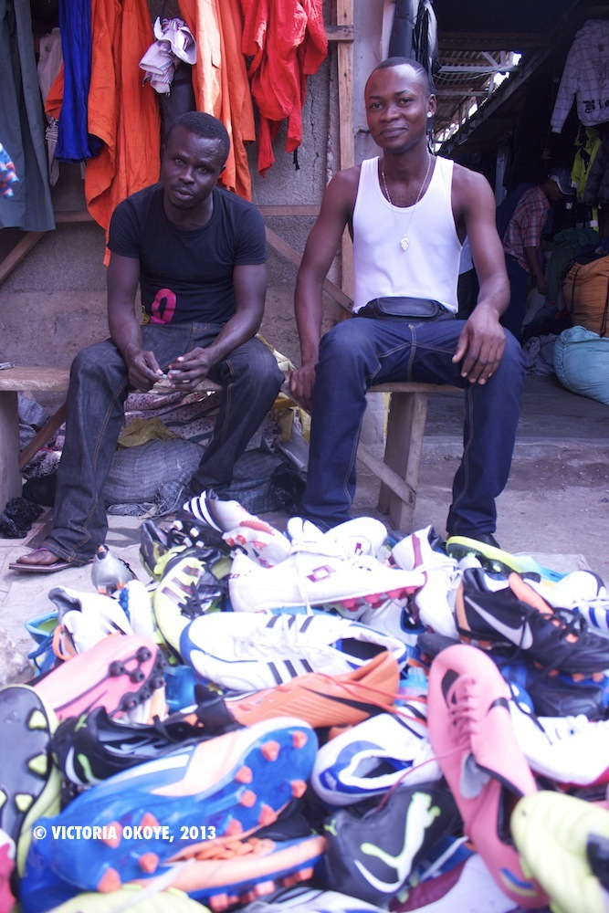 Two vendors, Boadi and Yaw Intim, sell used and new football shoes at Kantamanto Market in Accra.