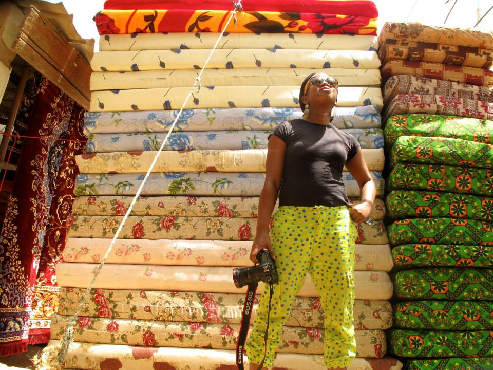 Invisible Borders photographer Jumoke Sanwo poses in front of beds in market in N'Djamena, Chad. (Photo Credit: Invisible Borders Trans-African Photography Project, 2013).