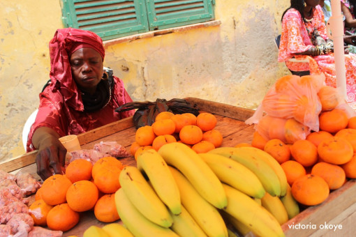 A fruit vendor sells bananas and oranges to residents and tourists.